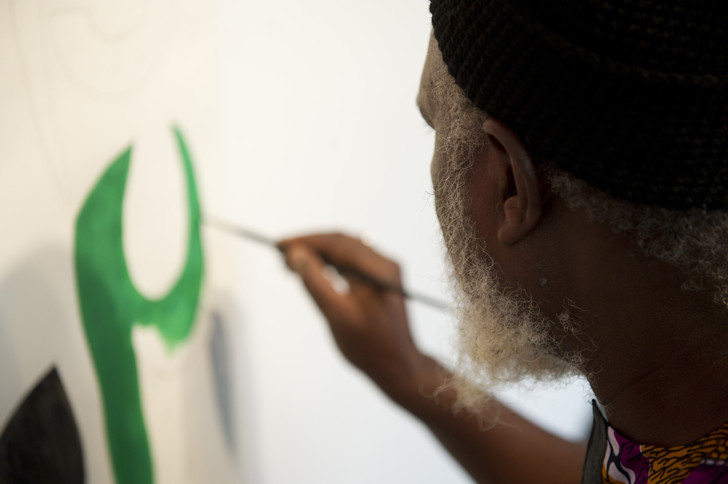 Artist Yelimane Fall of Senegal works on the beginnings of a mural while the rest of his work is installed for an exhibit in the GSU Gallery, November 9, 2011. Photo by Cydney Scott for Boston University Photography