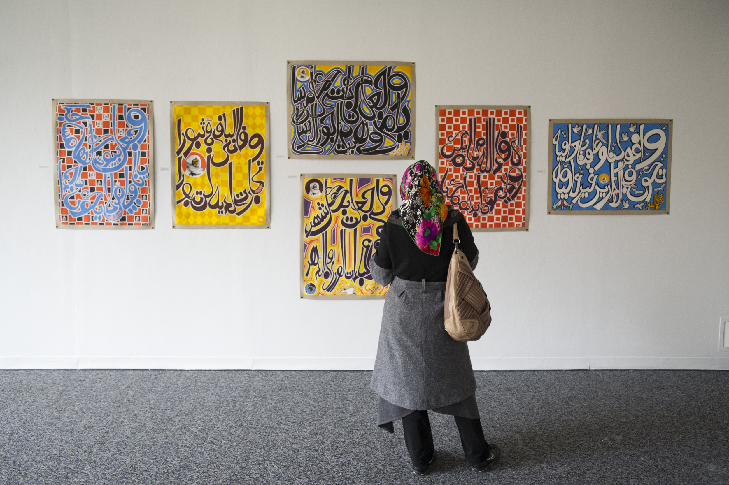 Zehra Kaya, who is from Turkey and is a BU CELOP student, admires the work of Yemine Fall, which is on display in the GSU Gallery.   Photo by Cydney Scott for Boston University Photography