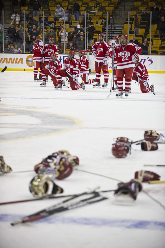 BC Eagles gear litters the ice as BU Terriers look on as the BC Eagles celebrate their overtime victory after the Men's Beanpot Final between BU and BC at the TD Garden on Monday, February 13, 2012.  Photo by Cydney Scott for Boston University Photography
