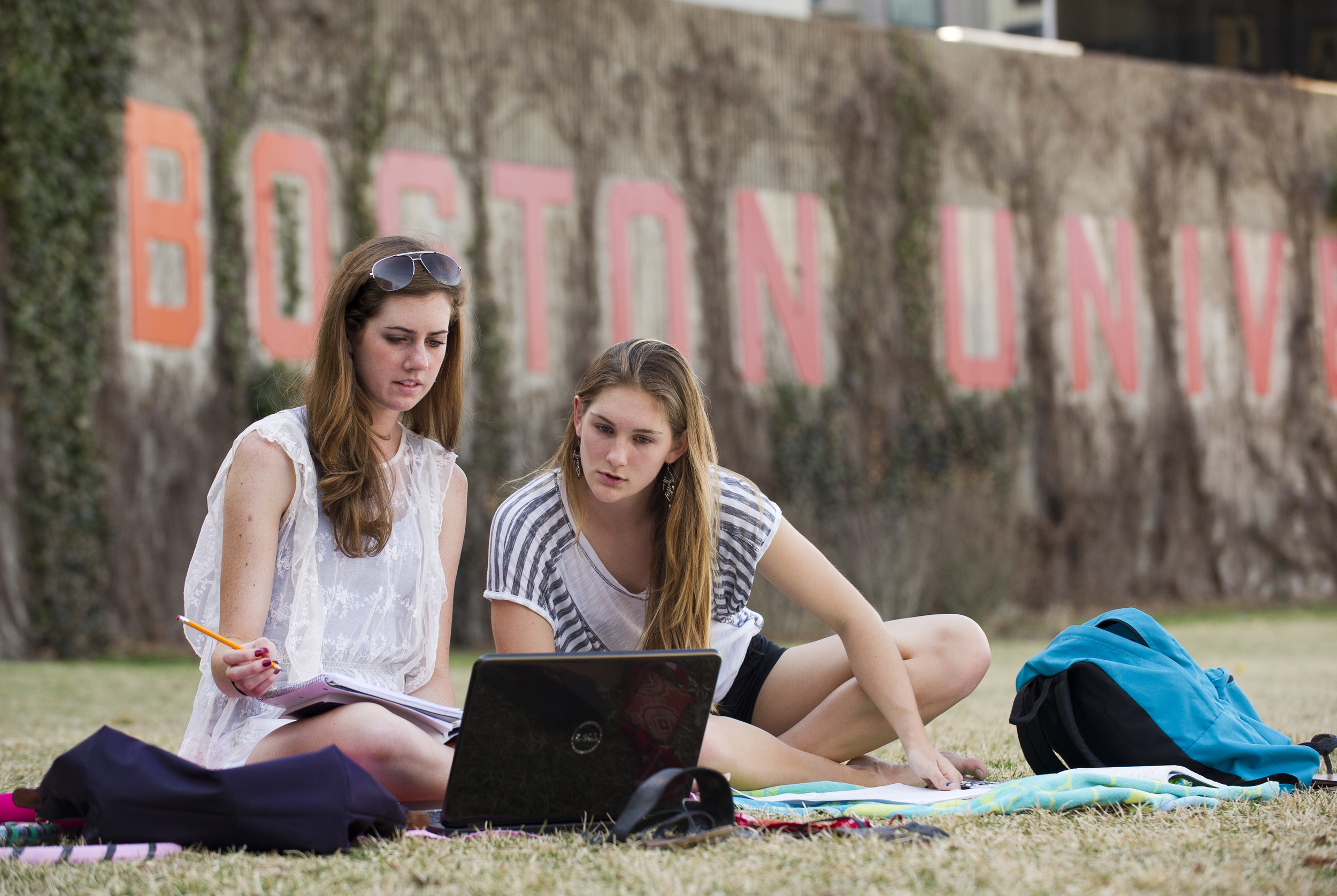 Kelsey Young (COM'15), left, and Boone Saunders (CAS'15) study statistics for class in the shade on Nickerson field. They had started in the sun, the two said, but it got too hot.  Nickerson field March 22, 2012.   Photo by Cydney Scott for Boston University Photography