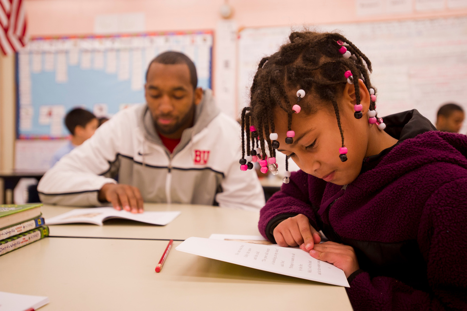 """BU basketball team member Travis Robinson (SMG'14), left, follows along with Ilanddy Peres while she reads """"Owl at Home"""" during the basketball team's recent visit to Sterling Scott's second grade classroom at Blackstone Elementary on December 13, 2012 for the16th Annual Boston University Athletics Holiday Reading Program. There are over 300 BU athletes and coaches participating in the event at various schools in the area.   Photo by Cydney Scott for Boston University"""