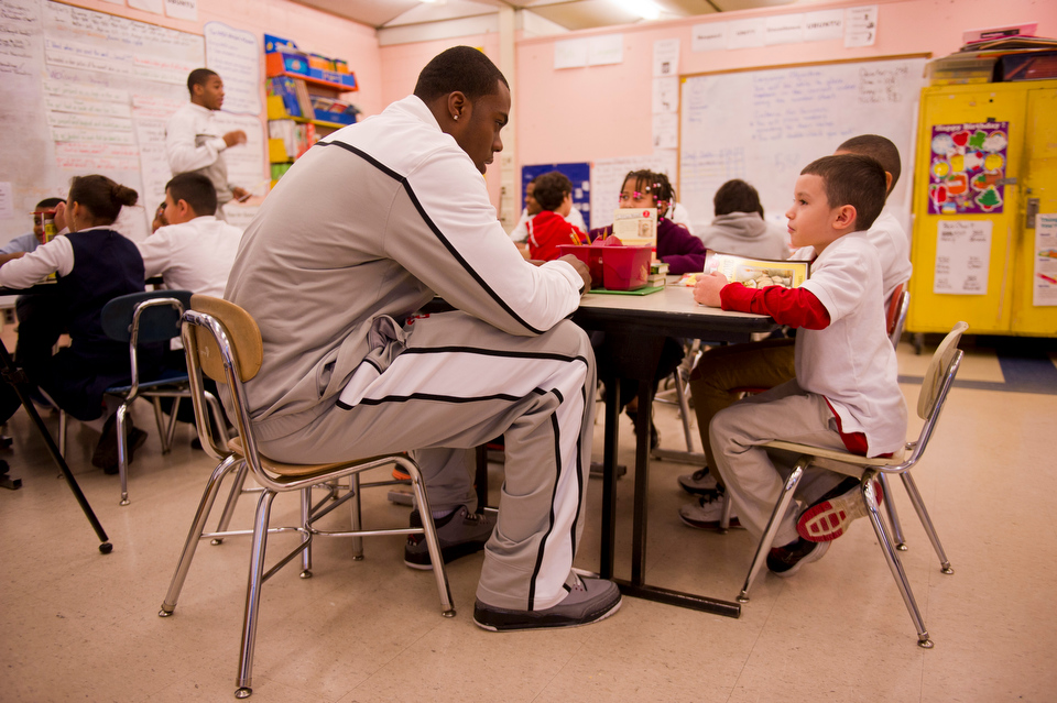 James Kennedy (CGS'15), left, chats with Henry Reynoso, a second grader at Blackstone Elementary, during a visit to the class Decemeber 13, 2012. Members of BU's basketball team read with children in Sterling Scott's second grade classroom at Blackstone Elementary on December 13, 2012 for the 16th Annual Boston University Athletics Holiday Reading Program in conjunction with the Office of Government and Community Affairs. There are over 300 BU athletes and coaches participating in the event at various schools in the area.   Photo by Cydney Scott for Boston University