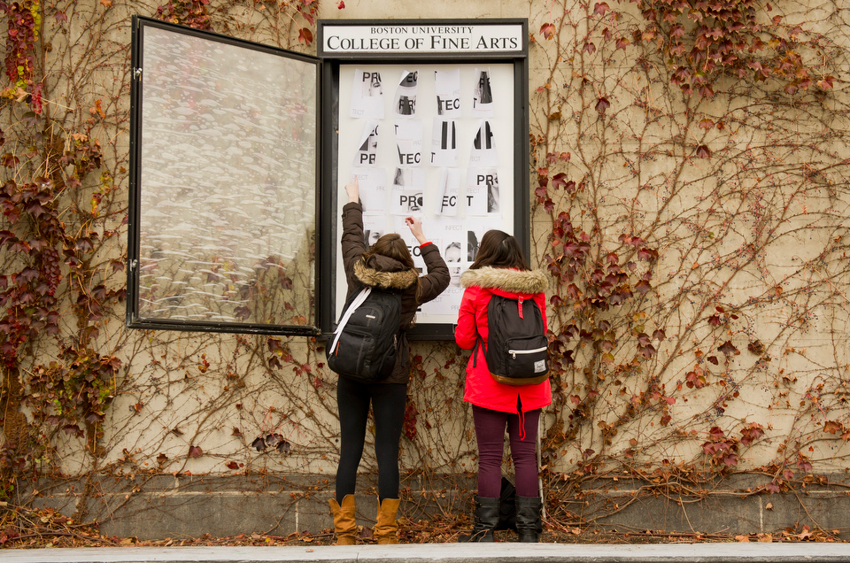 Courtney Schwabe (CFA'14), left, and Julie Ostrow (CFA, COM'14) works together to install Schwabe's World AIDS Day poster in front of CFA November 28, 2012. The two, and their other Junior Design Studio class mates were assigned to design posters for World AIDS Day which are comprised of fliers that can work alone or together in one piece. World AIDS Day is December 1, and other students' work will be displayed across campus.   Photo by Cydney Scott for Boston University