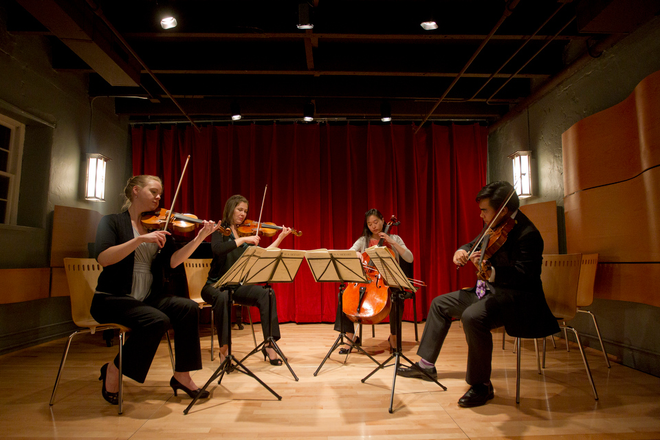 Heather Braun (CFA '08,'13), from left, and Rose Drucker (CFA'04), Agnes Kim (CFA'10, and BU string department faculty member Daniel Dona (CFA '05, '09) of The Arneis Quartet performs in Newton Upper Falls October 13, 2012 during the Carriage House Violins' opening night of Modern Makers 2012, an international exhibit of select instruments and bows by today's premier artisans.   Photo by Cydney Scott for Boston University
