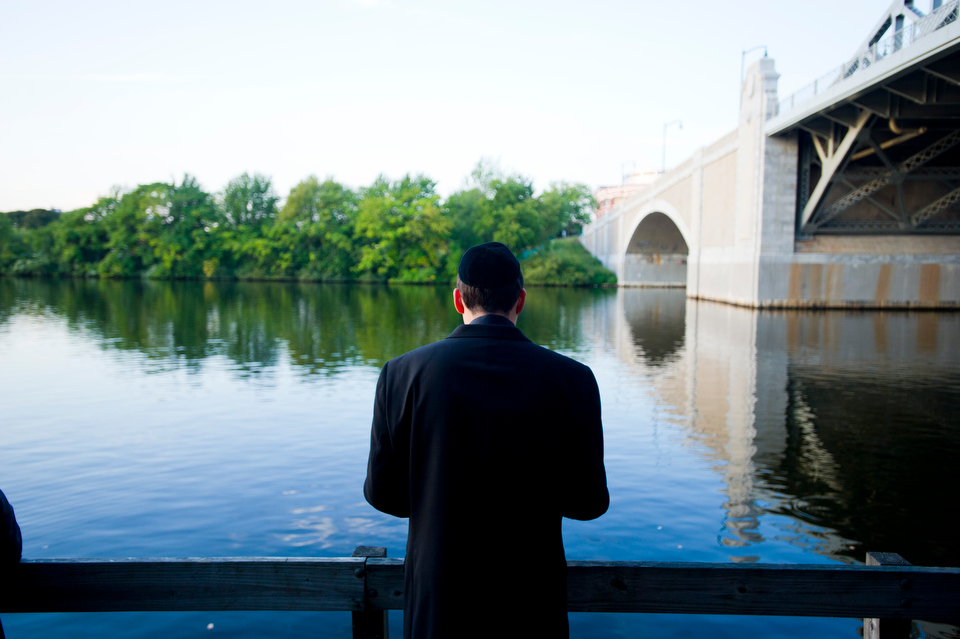 "Justin Wiemer (SMG,COM'13) observes a solitary moment for himself along the Charles River during Hillel House's observance of Tashlich Monday September 17, 2012. Tashlich often observed during Rosh HaShanah. ""Tashlich"" means ""casting off"" in Hebrew and involves symbolically casting off the sins of the previous year by tossing pieces of bread or another food into a body of flowing water. Just as the water carries away the bits of bread, so too are sins symbolically carried away. In this way the participant hopes to start the New Year with a clean slate. About 60 people participated in the Tashlich service this year. Photo by Cydney Scott for Boston University"