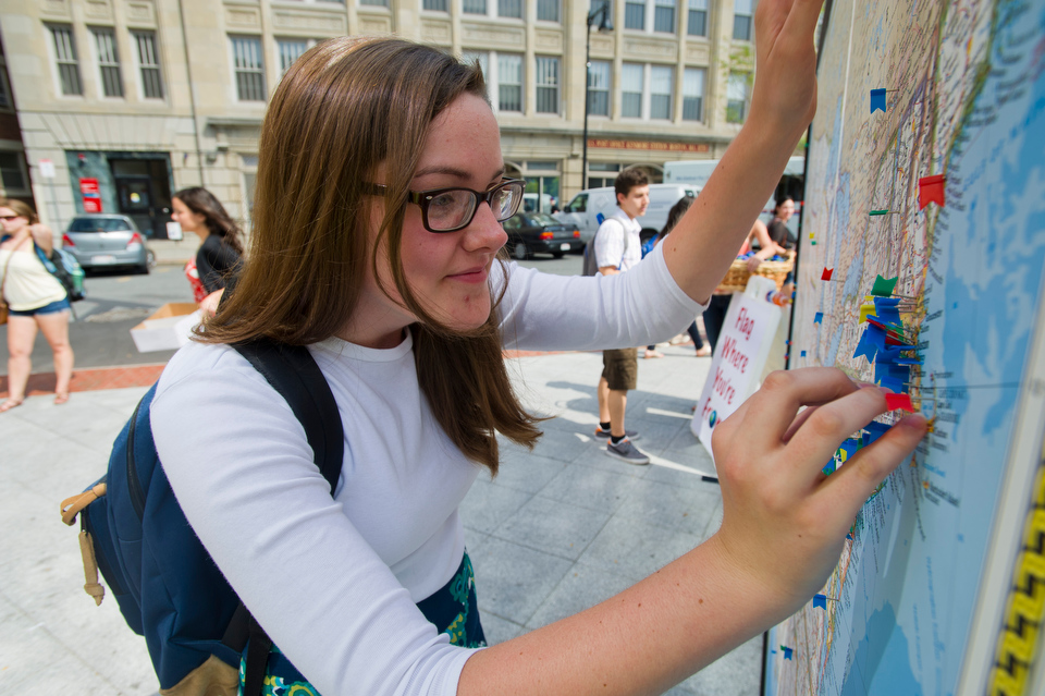 Michelle LeCorn (CAS'14) of Taunton, MA marks her hometown with a pin on a giant map located outside 100 Bay State Road during BU's Comm Ave Fair September 7, 2012. The world map was provided by the Student Program and Leadership Office.    Photo by Cydney Scott for Boston University