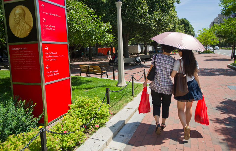 Jingyi Yuan (LAW'12), at right, and her mother Liu Xia of China stroll Comm Ave in some portable shade August 7, 2012. Liu is in town for a visit with her daughter for one month.  Photo by Cydney Scott for Boston University Photography