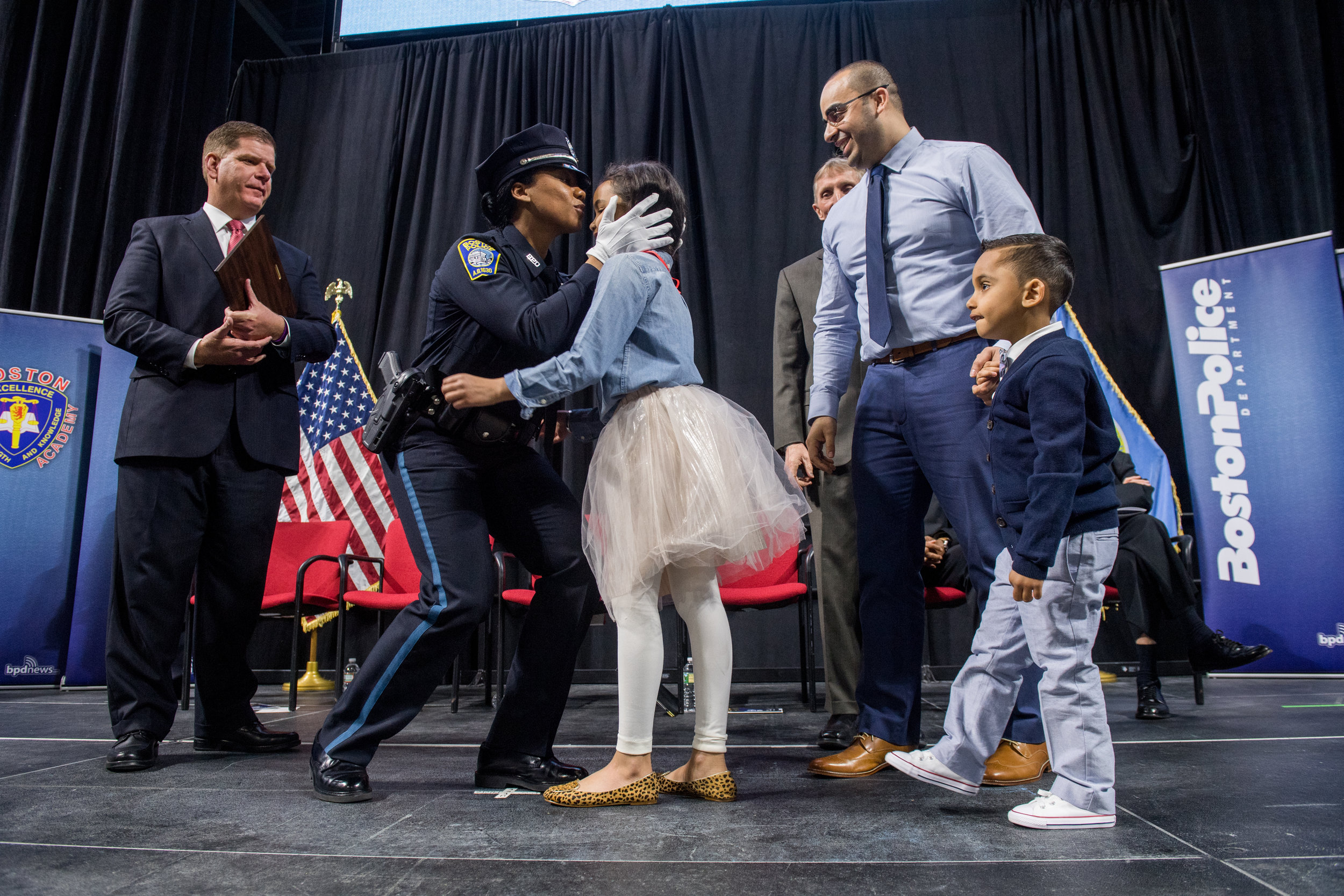 Jennifer L de los Santos kisses her daughter Nya, 8, after being pinned at the Boston Police Department Academy Graduation Class 57-17 April 10, 2018 at Agganis Arena. Looking on are Mayor Martin Walsh at left, Police Commissioner William B. Evans third from right , de los Santos' husband Jason, and their son Jace de los Santos, 4. Not pictured is their third child Jonas, age 2.