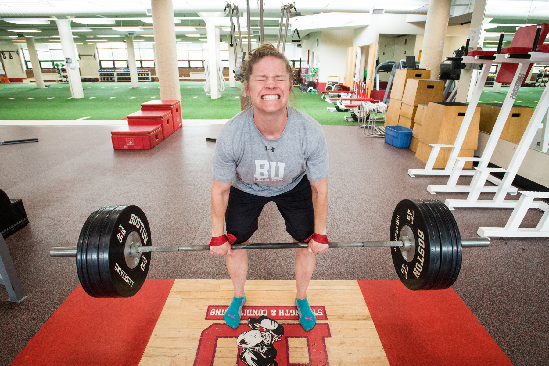 """BU Athletics associate strength and conditioning coach Darcy Gould dead lifts 265 pounds in the weight room June 5, 2018. Gould, who works with women's ice hockey, softball, lacrosse, and women's lightweight rowing lifts weights herself four times a week. """"I like the accomplishment of every set, every lift. There's no blaming anyone else (if you fail to lift). Either you do it or you don't"""" said Gould."""
