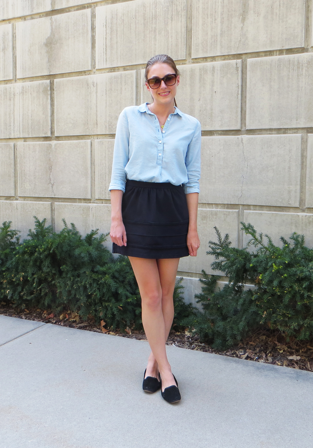 Classics: light blue popover shirt, black mini skirt, black loafers, monogram necklace -- Cotton Cashmere Cat Hair