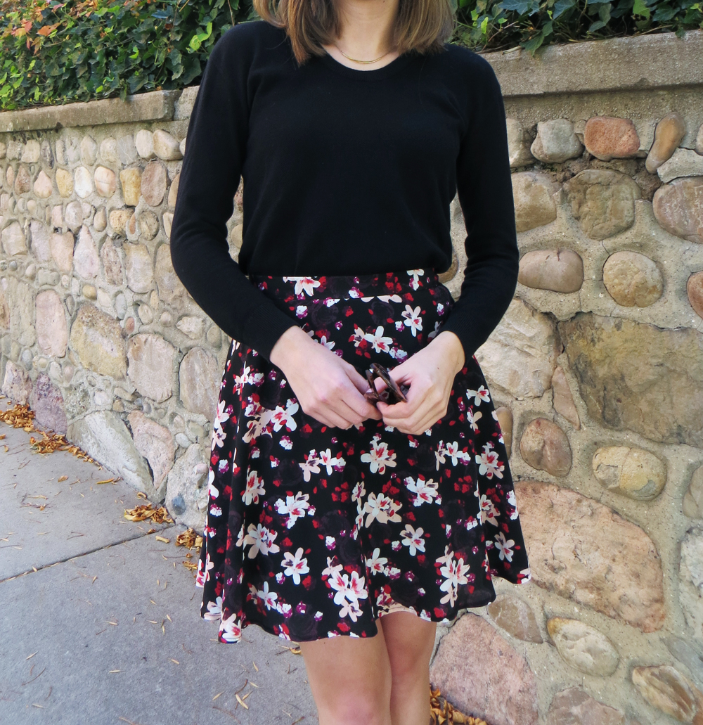 Black sweater, dark floral skirt, simple necklace -- Cotton Cashmere Cat Hair