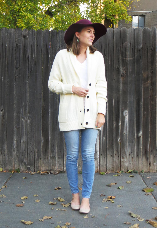 Ivory knit cardigan, white tee, light wash denim, burgundy hat, emerald green earrings -- Cotton Cashmere Cat Hair