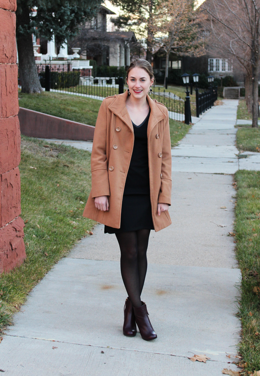 Camel coat, black sheath dress, dark red ankle boots, statement earrings — Cotton Cashmere Cat Hair