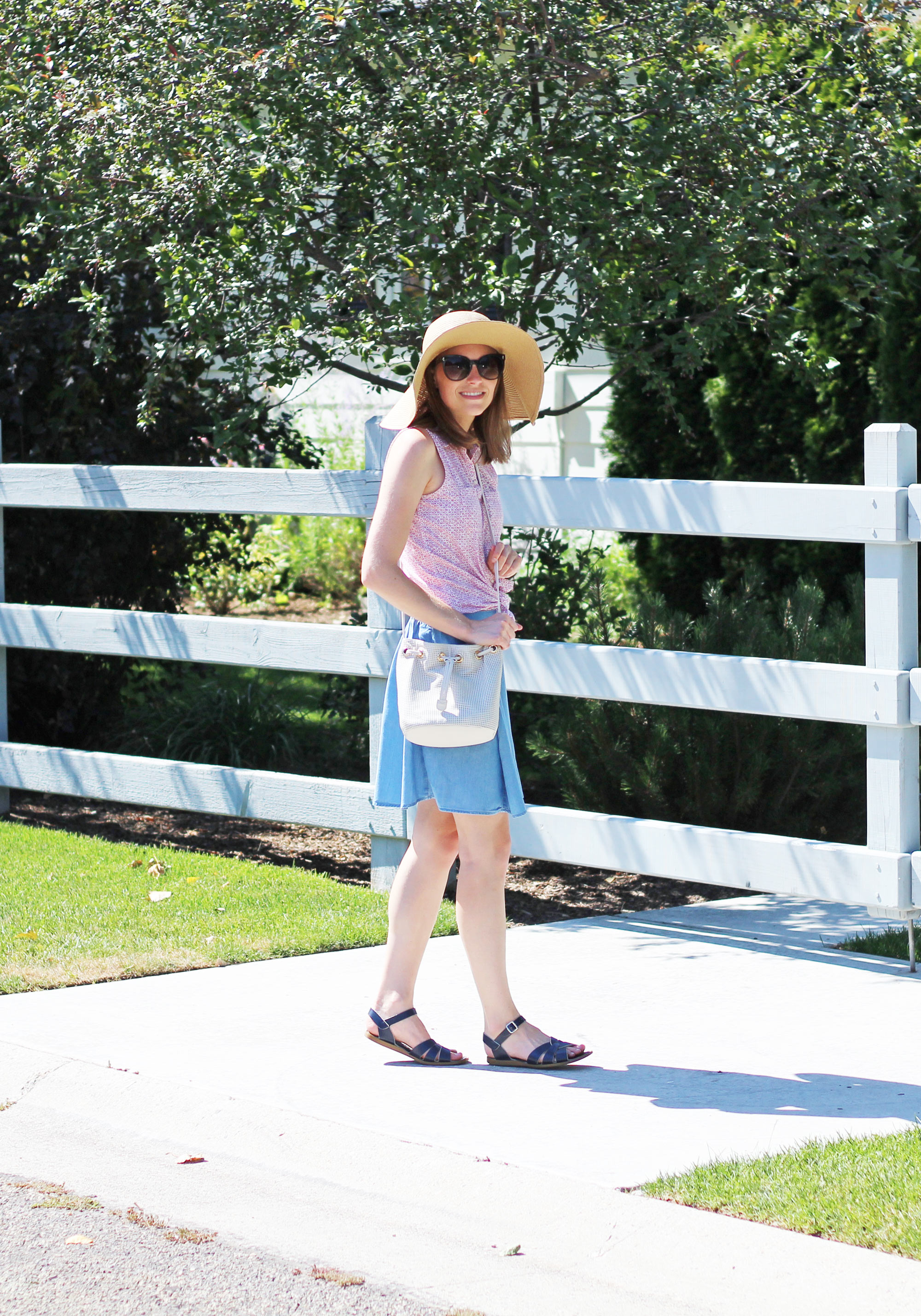 Red floral shirt, chambray skirt, navy Salt Water sandals, floppy sun hat, white bucket bag — Cotton Cashmere Cat Hair