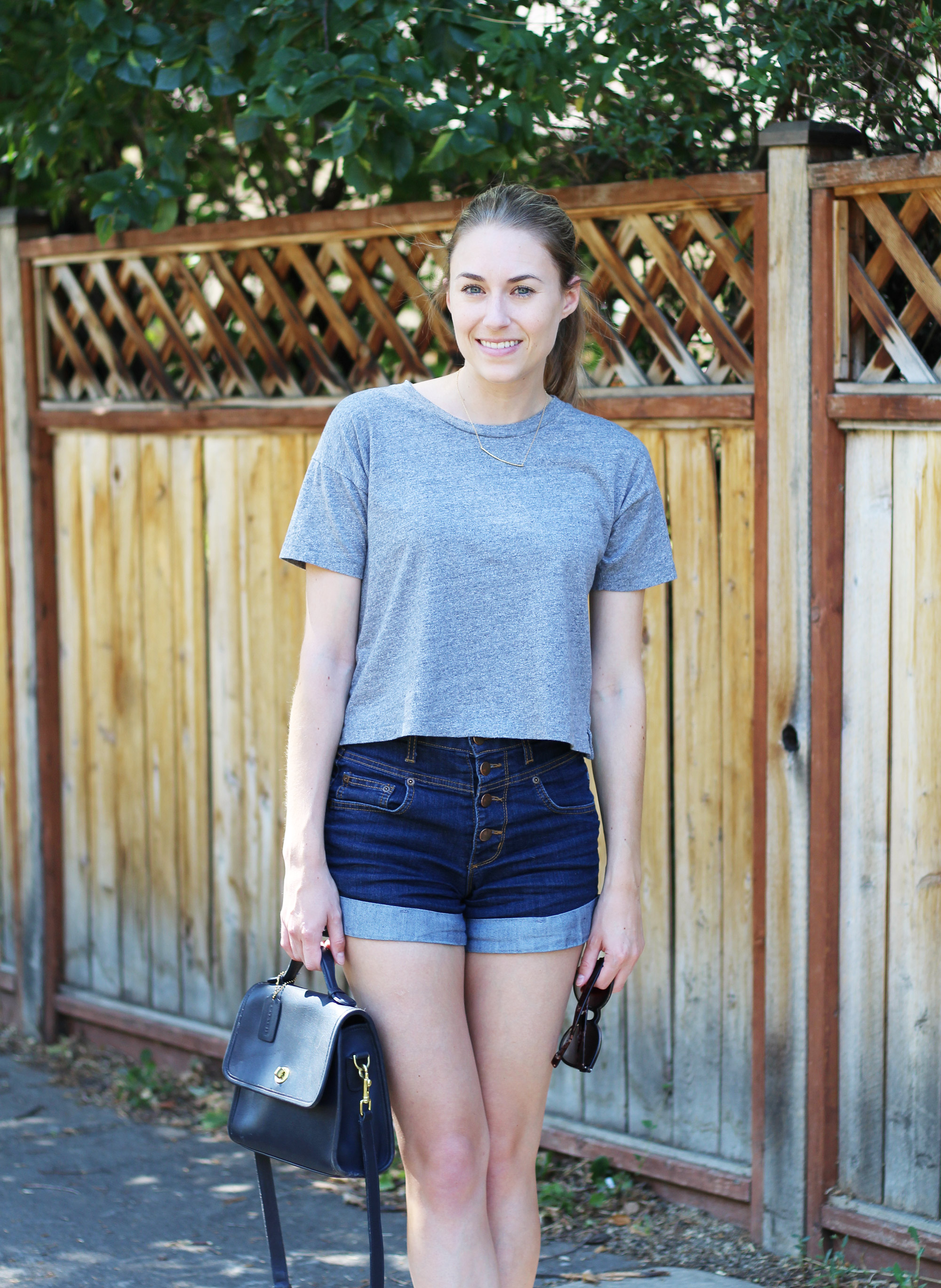 Grey cropped tee, high rise denim shorts, navy Coach 'Court' bag — Cotton Cashmere Cat Hair