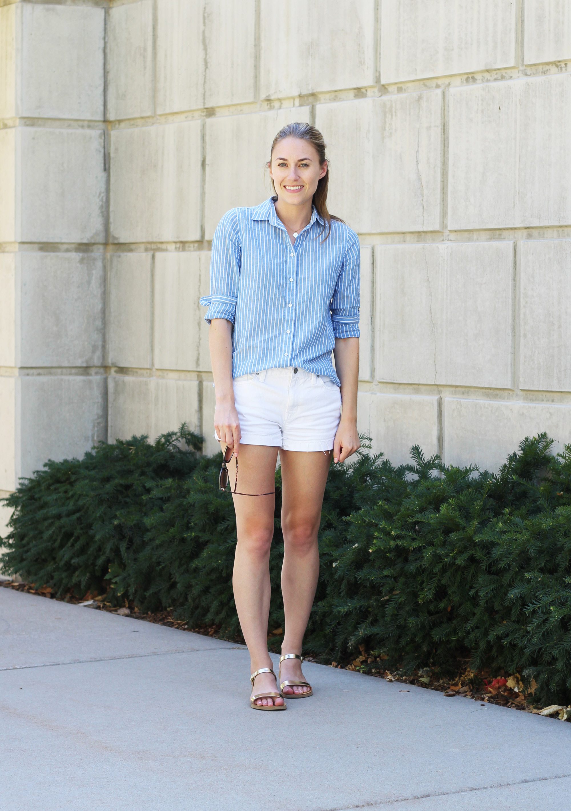 Simple summer outfit: Blue striped shirt, white denim shorts, gold sandals — Cotton Cashmere Cat Hair