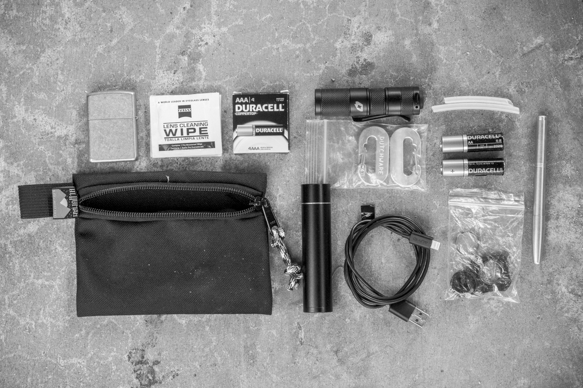 Zippo Lighter, Glasses/Lens Wipes, AAA Batteries, FourSevens Quark QTL Flashlight, Dutchware Carabiners, Ravpower Charger, Lightning/USB Cable, Plastic Tubing, AA Batteries, Flashlight Accessories/D-Rings/O-Rings, Machine Era Brass Pen with 0.5 Juice Refill.  It's amazing that all this stuff fits in this one teeny, tiny pouch.