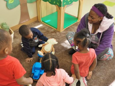 """Teacher Dasheena Moore practices the 14 Talking Tips with children in her classroom. """"The tips have helped me get my kids talking more by following their lead and paying attention to what they're interested in,"""" she said."""