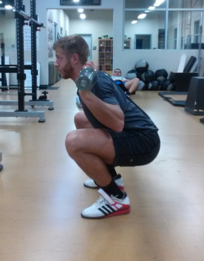 Hamstring and calve contact should be made to ensure full-depth is being achieved. The chest should remain tall without the lower back rounding. Toes angled slightly out, while driving the knees out to create a hole to sit into. Head is in a neutral posture, and arms are tight enough in on the bar to create a shelf with the traps for the bar to sit on (this picture is a high-bar Olympic styled squat).