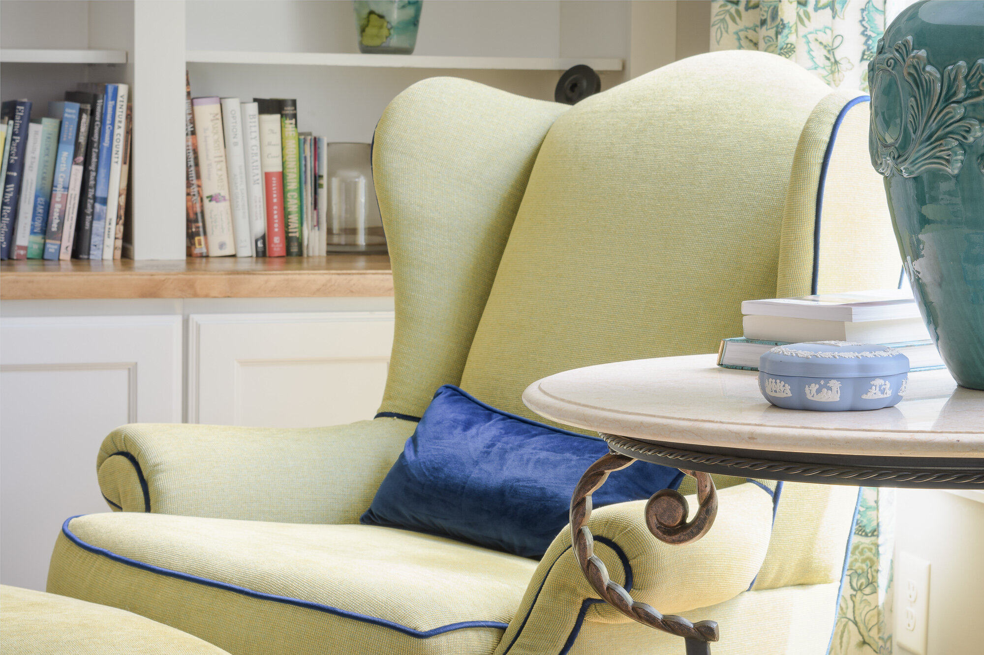 Quality chair reupholstered in green fabric with custom blue accents.