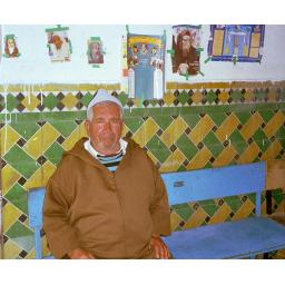 "Hananiyah Elfassie, the last Jew in the Ourika Valley of Morocco's High Atlas mountains, guards the tomb of a ""Tzadik"" who died 500 years ago. Foreign pilgrims visiting the Tzadik's tomb taped snapshots of famous rabbis to the wall behind him."