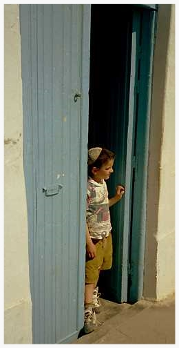"On Friday afternoon, the old men in one of Hara Kebira's many synagogues nod off in the stifling heat, waking periodically to chant or argue Talmud. Suddenly, a Djerba boy showing tsit-tsit (fringes of an undershirt prayer shawl) runs into the doorway, looking for his friend. ""Mikhael!"" he yells into the sanctuary. The learned scholars do not even seem to notice. While waiting for friend Mikhael to retrieve the soccer ball, the boy observes with curiosity a foreigner behind him in the street. Pointing to his head, the boy addresses the man inquisitively, ""Kipah?"" stating the Hebrew word for yarmulke or skullcap. Growing up on an island, in the last Jewish village in North Africa, and spending his youth in cheder (Hebrew school), the boy is confused. He seems to wonder, ""This man does not look like an Arab, yet he wears no kipah like the Jewish men. Should I invite him to play or not?"""