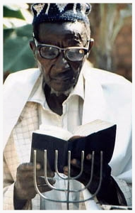 Kezikia Bumba, eighty year old President of the Abayudaya Men's Club, was one of the first converts to Judaism in the hills surrounding Mbale, Uganda, in the 1920s. Bumba learned about Judaism from the community's founder, Semei Kakungulu, and passed his knowledge to younger Abayudaya as a religious instructor and prayer leader. Today Kezikia Bumba still practices the Judaism Kakungulu taught him, blending Hebrew prayer with songs and chants in Luganda, the local language. Bumba works as a welder, and in his spare time welds menorahs for his Abayudaya neighbors.