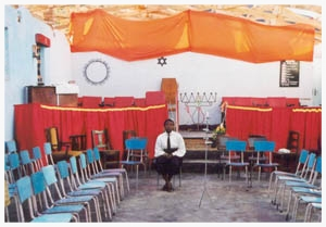 After Shabbat services outside of Rusape, Zimbabwe, Grace sits by herself in the empty tabernacle.