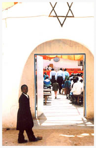 """Every Saturday morning over a hundred members of the Rusape, Zimbabwe, Jewish community gather at their """"tabernacle"""" for Shabbat prayers. Members of the community, young and old, wear their absolute best -- brown three-piece suits for the men and brilliant turquoise blouses and jeweled hair wraps for the women."""