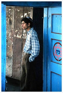 "Dayan Samson Penkar stands at the doorway to Beth Ha Elohim, the 130 year-old synagogue in Pen, a village two hours southeast of Bombay. Bene Israel historians tell that when seven, exiled Jewish couples first shipwrecked on the Konkan Coast nearly 2000 years ago, they believed they would not stay long. As they scattered to villages, they took their father's (or, if married women, their husband's) names as second names (e.g., in Dayan's case, Samson). They assigned surnames (e.g, Penkar) with the name of their village (in this case, Pen) and the suffix ""-kar,"" meaning in the local language, ""a sojourner."" Centuries later, nearly all of the Bene Israel – like most of their non-Jewish, Maharashtrian neighbors, have surnames ending in '-kar.' Today, fewer than 10 Bene Israel families live in Pen, most with the last name ""Penkar."""