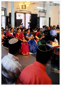 "The Jewish community watches as two young Bene Israel siblings marry arranged Bene Israel partners on the same day at Thane's Magen Hassidim Synagogue, India's largest congregation. Chazzan Benny Dandekar made both matches. As children, the brides and grooms studied Hebrew prayers with Benny, and he remained close to their families. ""Many people used to do the job of matchmaking,"" Benny recalls. He considers himself blessed to be one of the few left in this role: ""The chosen man from the chosen people!"" Benny is fond of saying."