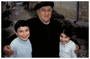 "Shammai Menachemovitch Israelov stands with his grandchildren, young Shammai (pictured at age 10) and Ruga (pictured at age 8), on the street where he has lived for more than seven decades. The elder Shammai worked 52 years as a telephone operator in Quba, the Azeri town that abuts Krasnaya Sloboda. He says the biggest difference between the Communist period and the present regime is ""what we built, what we earned."" ""We lived peacefully under the flag of the Soviets,"" Shammai recalls. ""It was a good time. There was enough money for everything."" Now, Shammai's hard-earned pension has been gutted and the costs of necessities are skyrocketing. Nonetheless, Shammai will not let a Krasnaya Sloboda visitor escape town without enjoying a meal with his family in his life-long home."