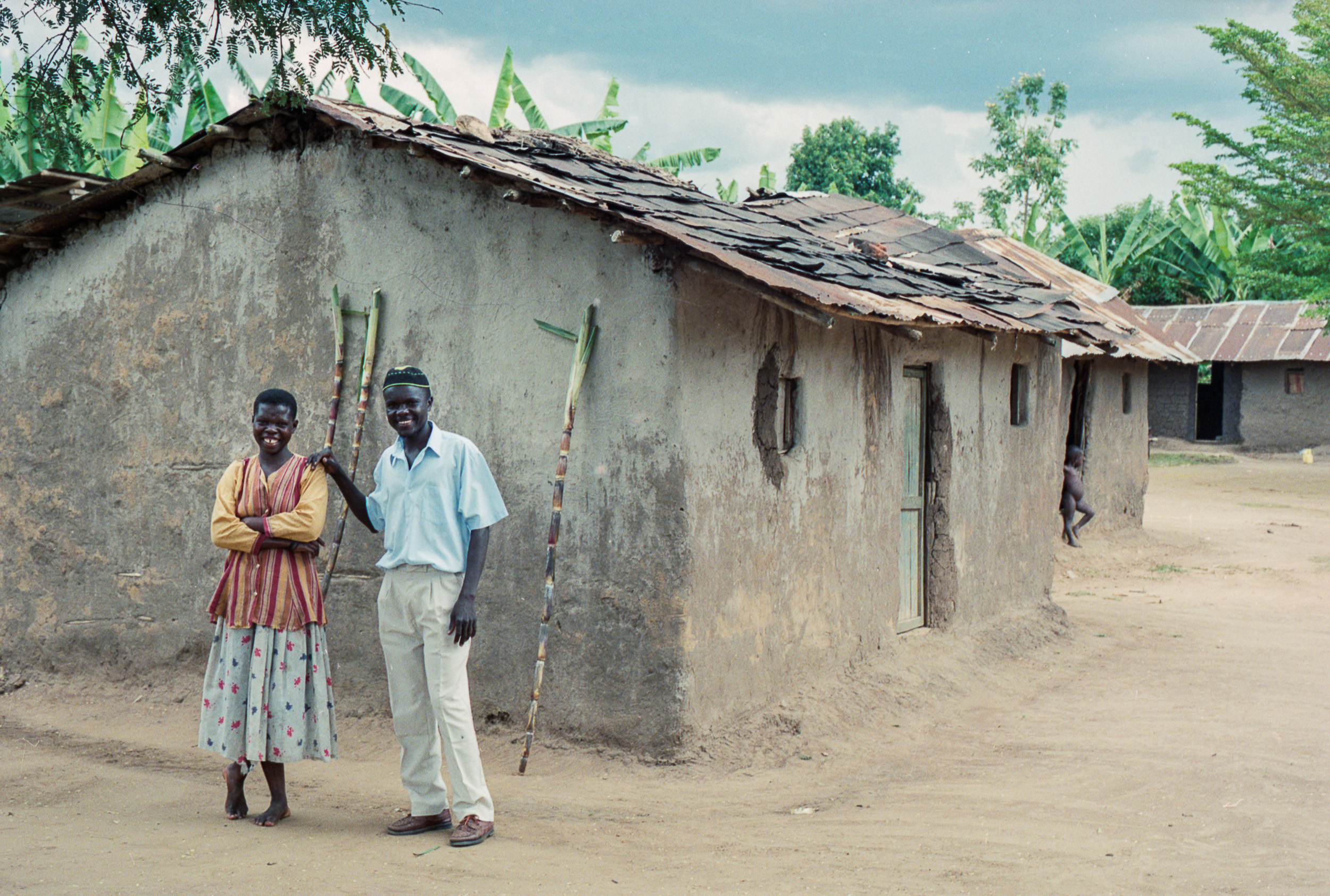 Athaliah Deborah and her husband Musenze Pinehas in front of a typical Eastern Ugandan home. The sugar cane behind them is from a nearby field.