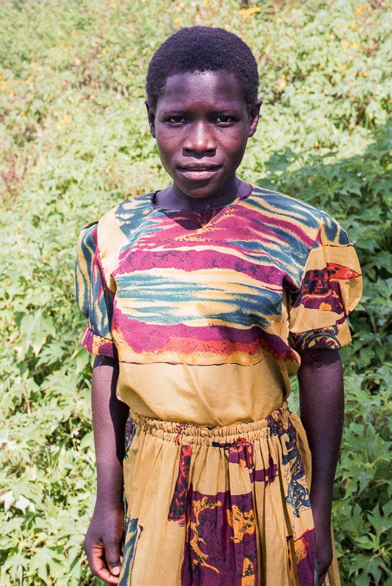 An Abayudaya woman wears a traditional, brightly-colored Ugandan dress.