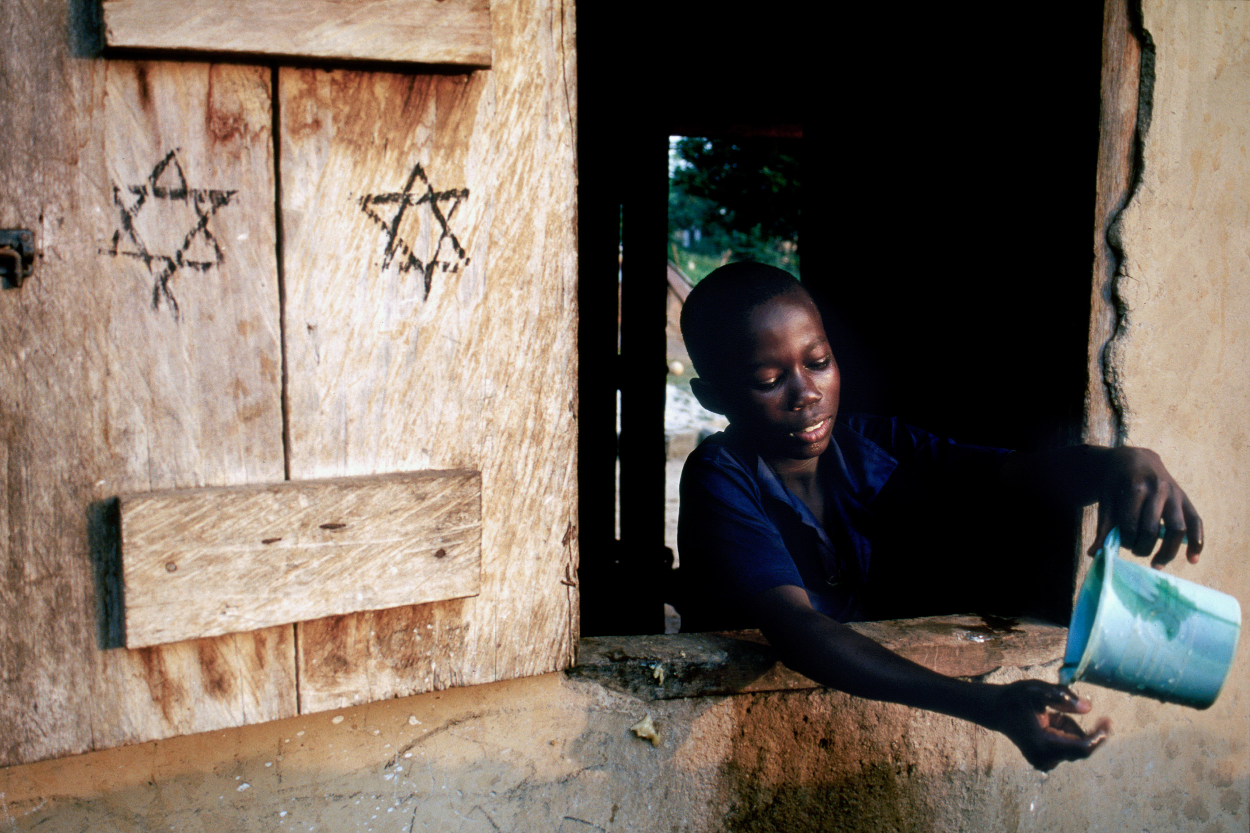 After helping to prepare the Shabbat meal, Kwame Armah leans out the window of his family's kitchen and cleans his hands before nightfall. Children comprise many of the hundred or so members of Ghana's House of Israel community. Unlike their parents, most of whom chose Judaism as their religion while they were adults, the children of the community have grown up with Shabbat, nightly meetings to learn about Judaism, and a strong connection with the Jewish people.