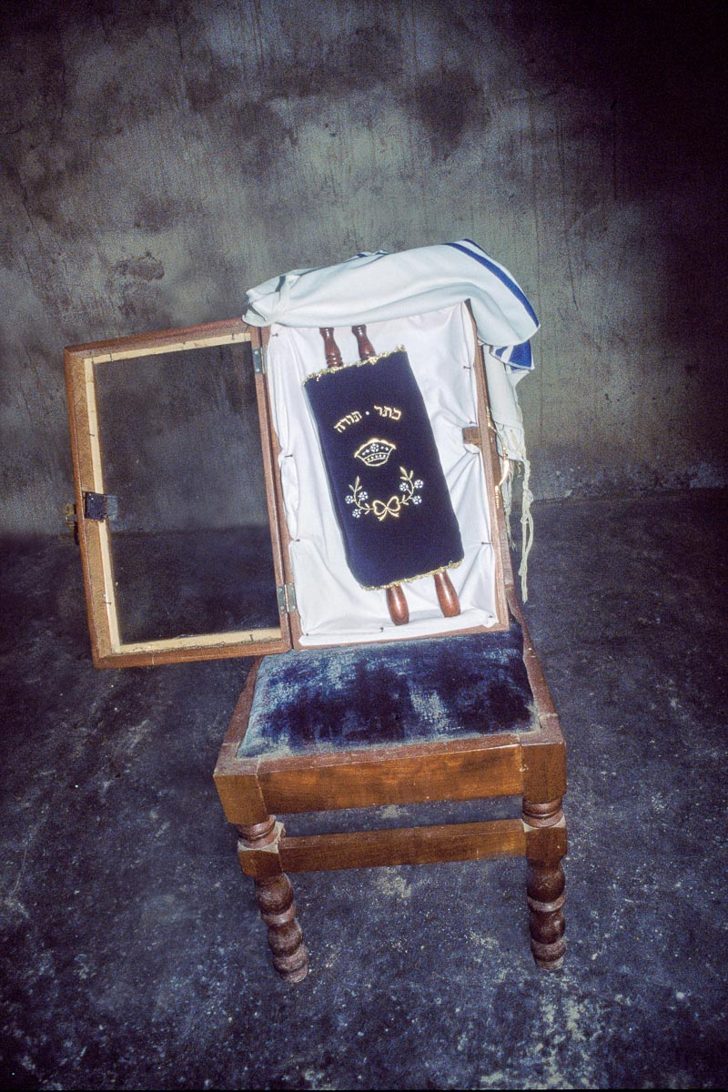 The House of Israel community's miniature Torah is housed in Tefereth Israel synagogue in a glass and wooden case, which rests on the seat of a chair and is typically covered with a tallit. The Torah, carried to the community by Washington, DC-area resident Daniel Baiden, is removed from the ark every Shabbat morning. Though it is tiny, the community loves this Torah.