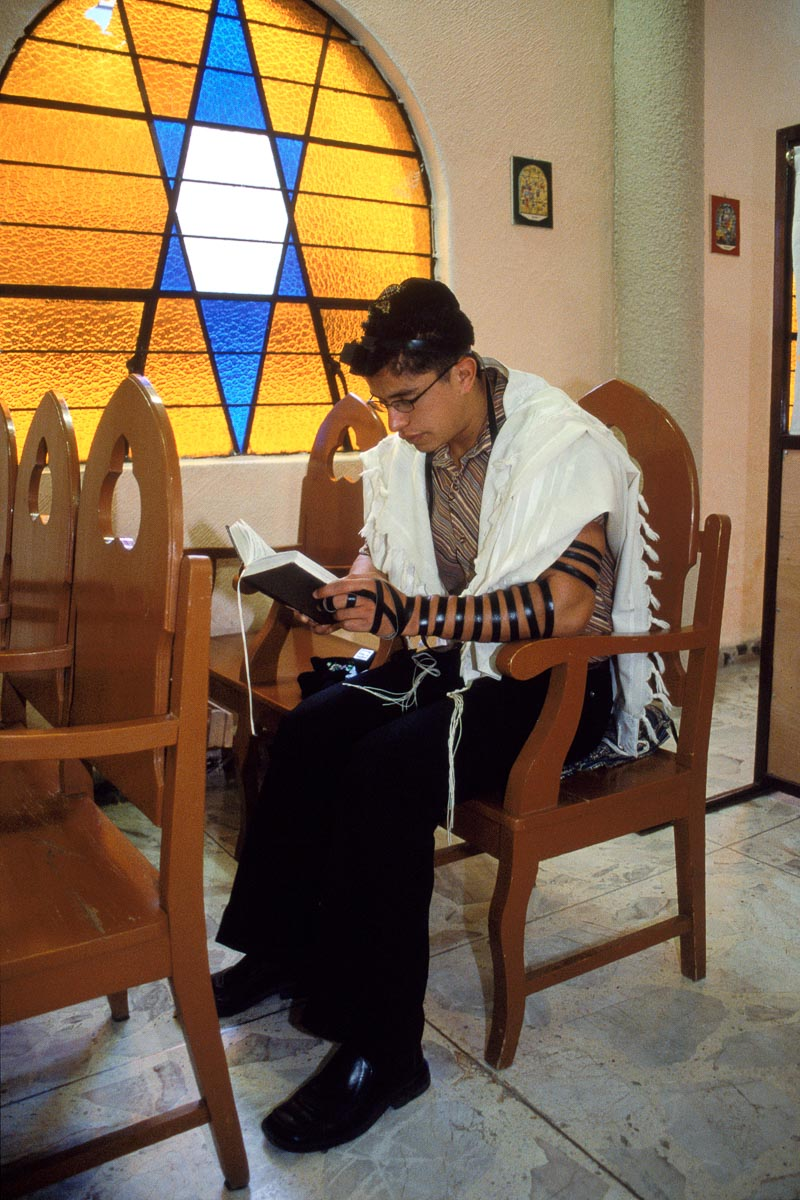 Men from Venta Prieta gather daily as morning light filters through the stained-glass windows of the Negev synagogue. They pray the morning  Shacharit service, each wearing a  kippah ,  tefillin (phylacteries) and  tallit  (prayer shawl).