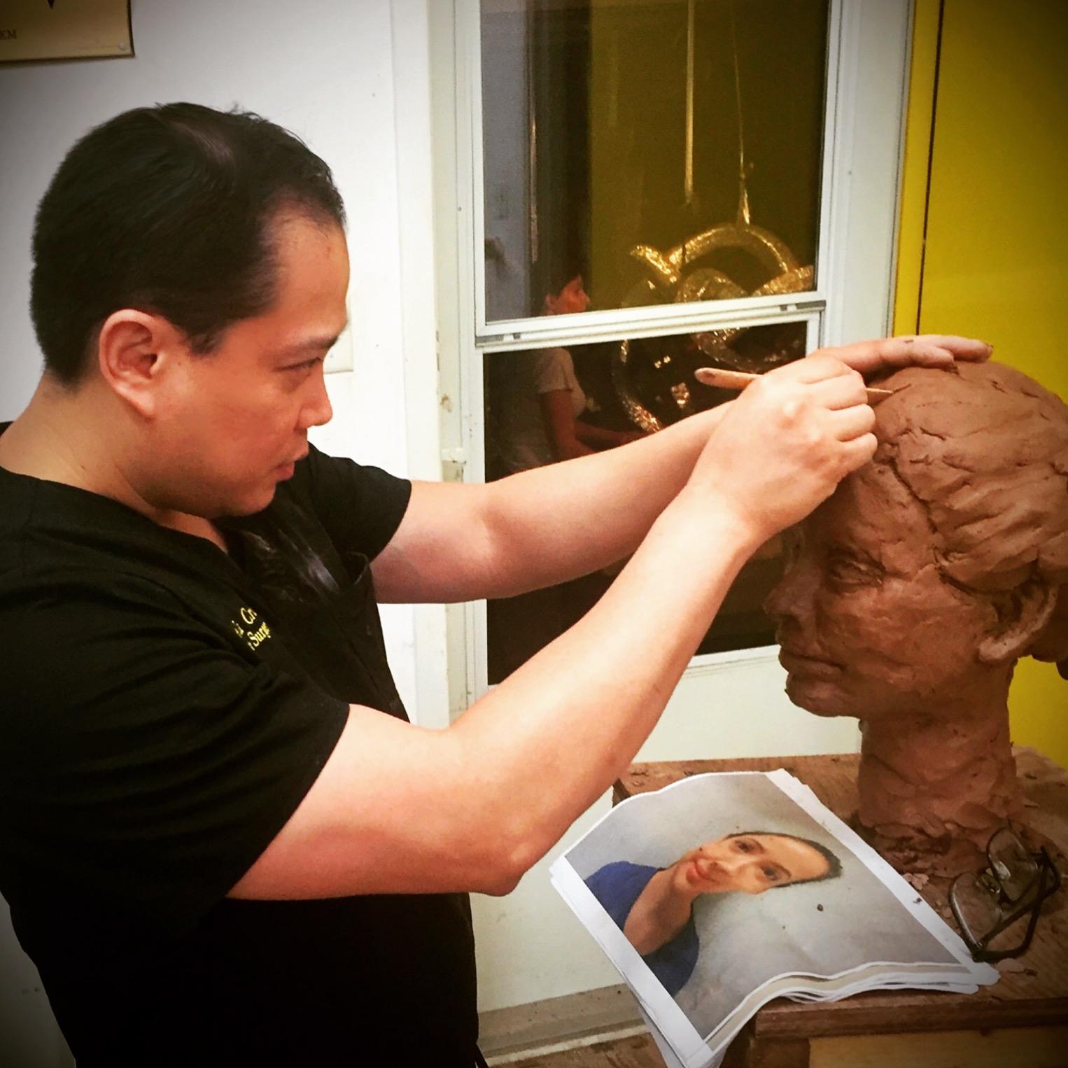 Dr. De La Cruz finishing his portrait sculpture.