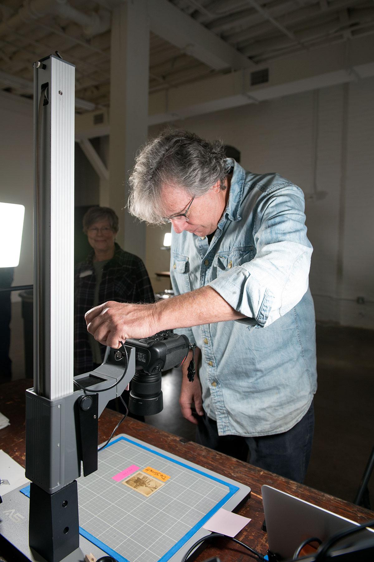 Photographer Nash Baker copies a damaged photo. /  photo by Jim Parsons