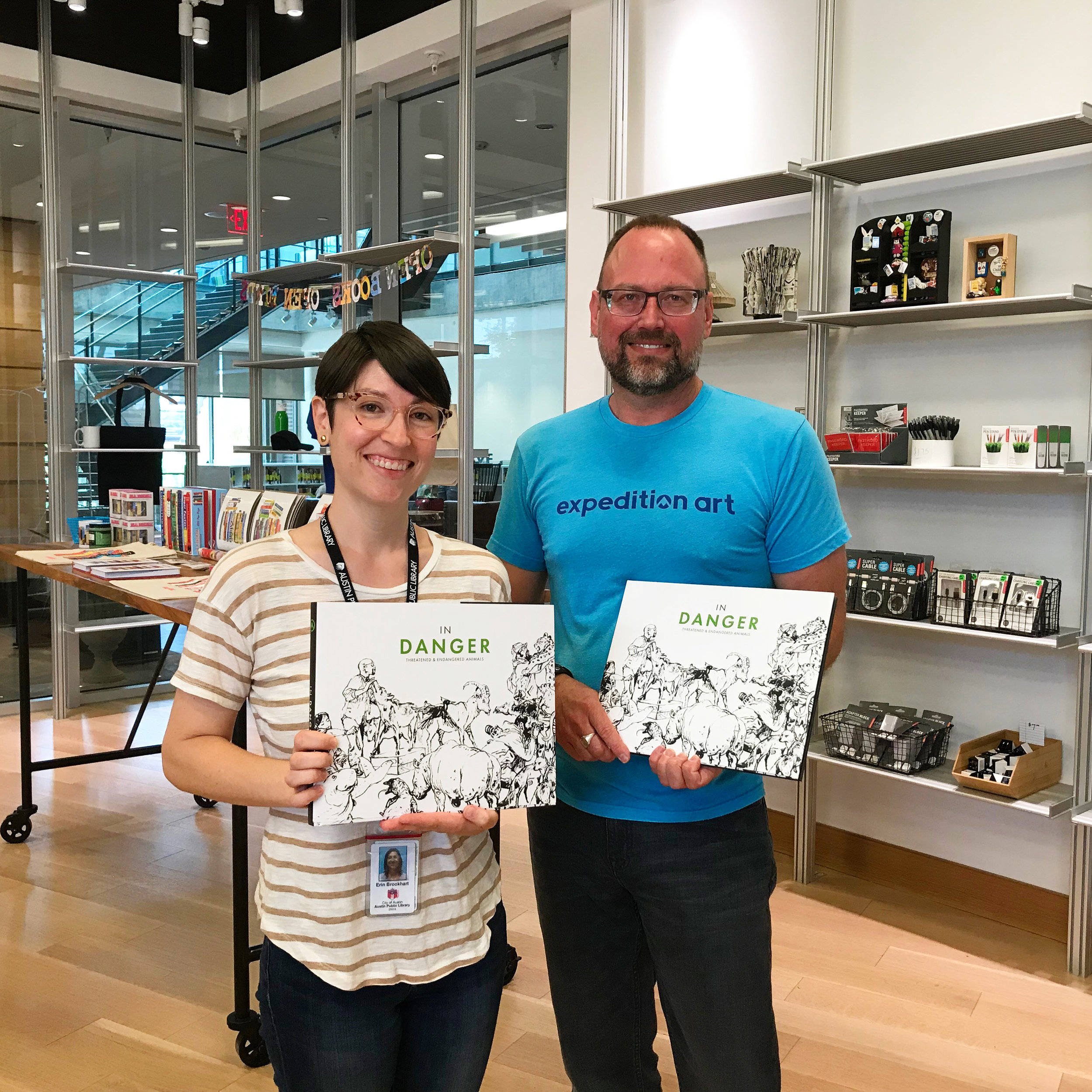 Recycled Reads Gift Shop manager,  Erin Brookhart  with Expedition Art's John Tipton.