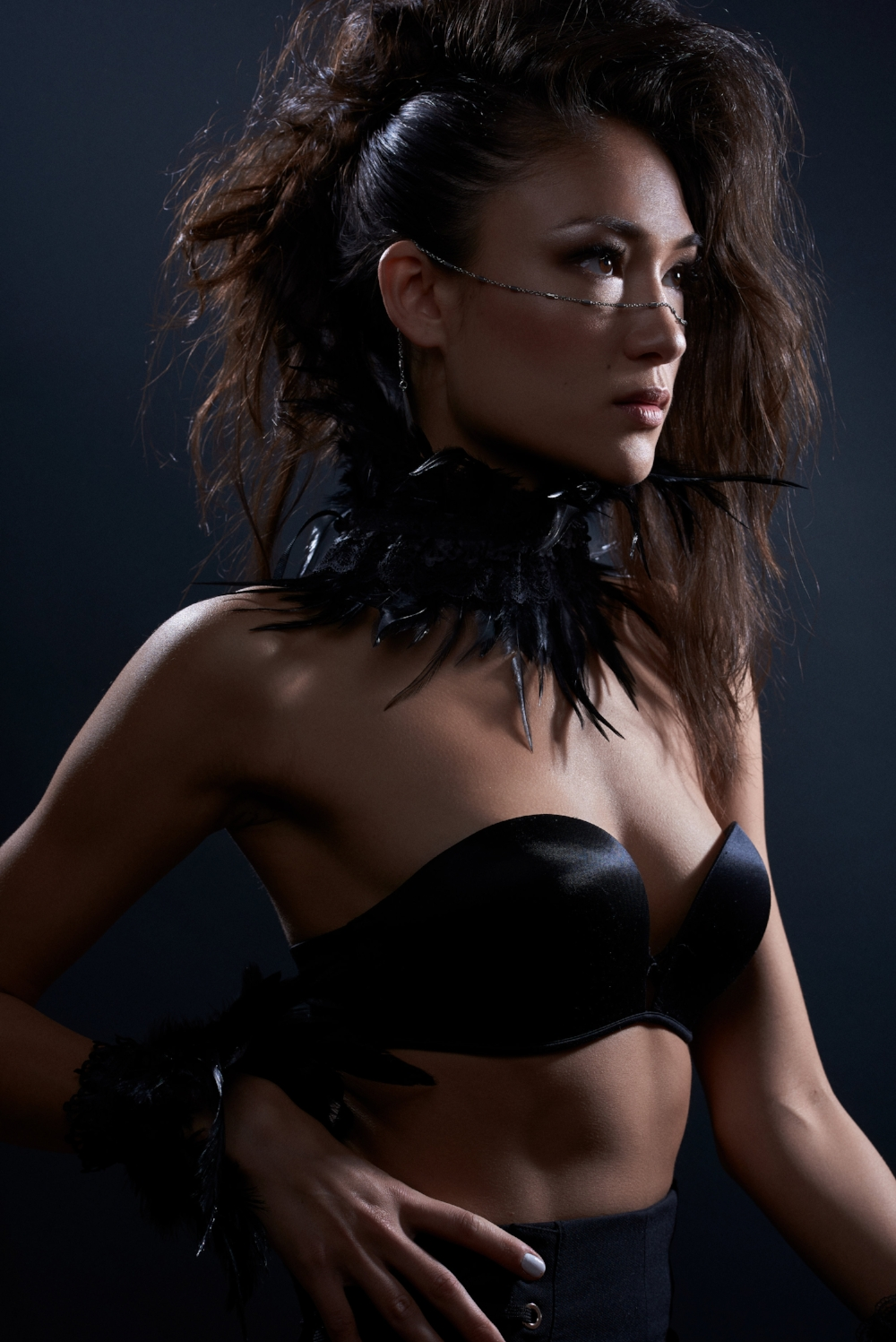 oriental model wearing feather collar with black strapless bra and vadana face jewellery