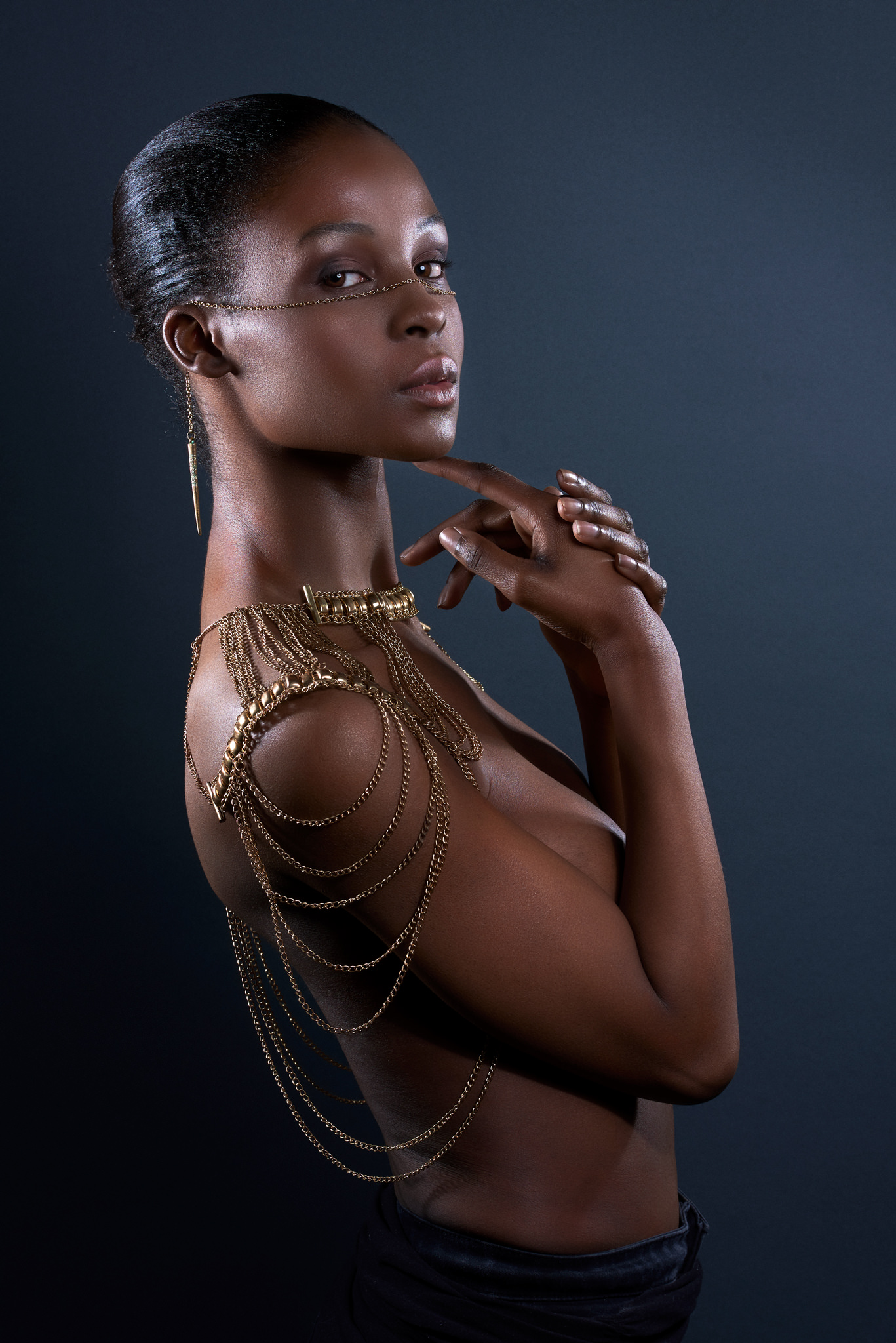 topless  black model covering herself wearing body and face jewellery fashion editorial