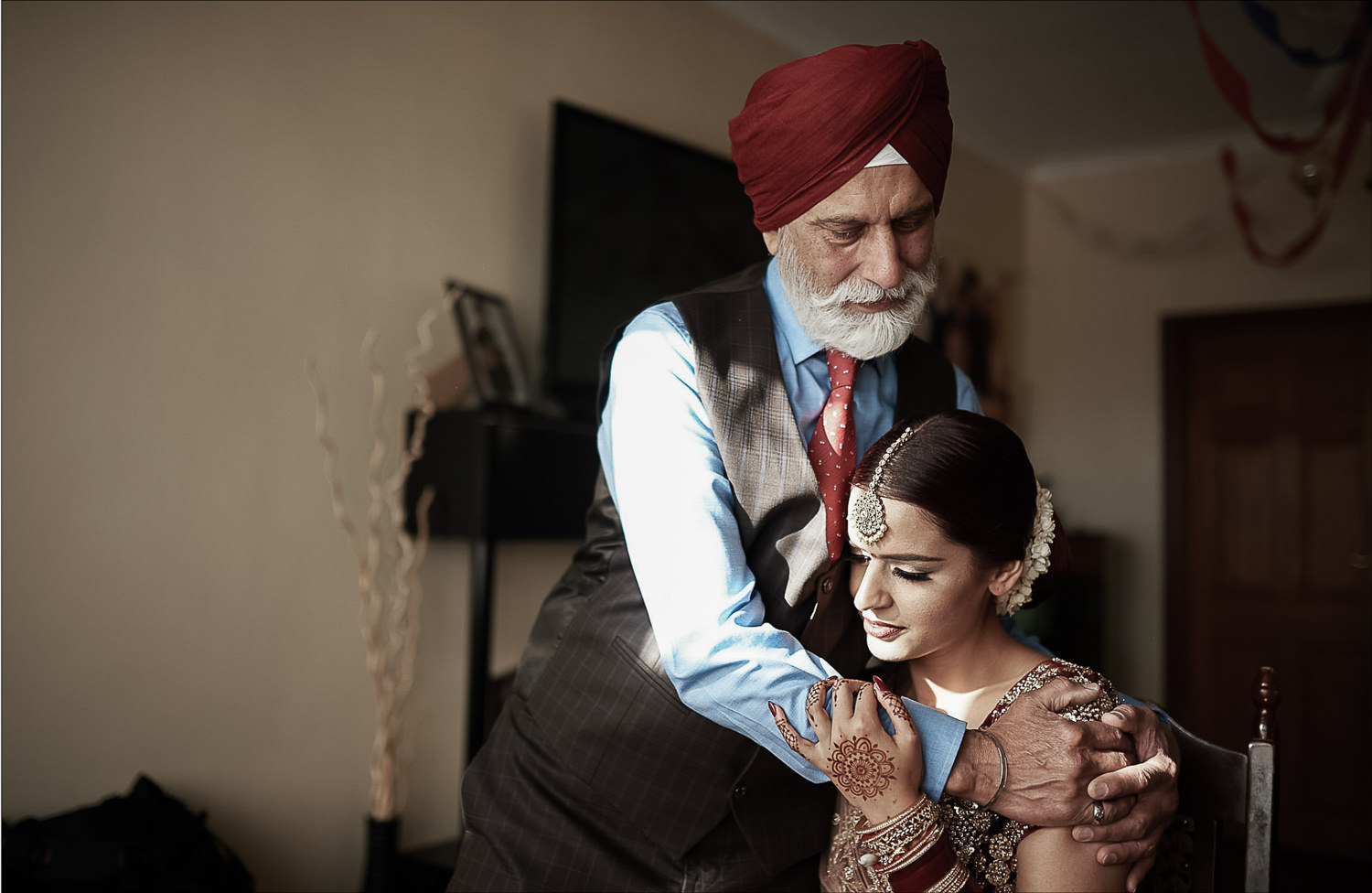 Father hugging Indian bride before she leaves home