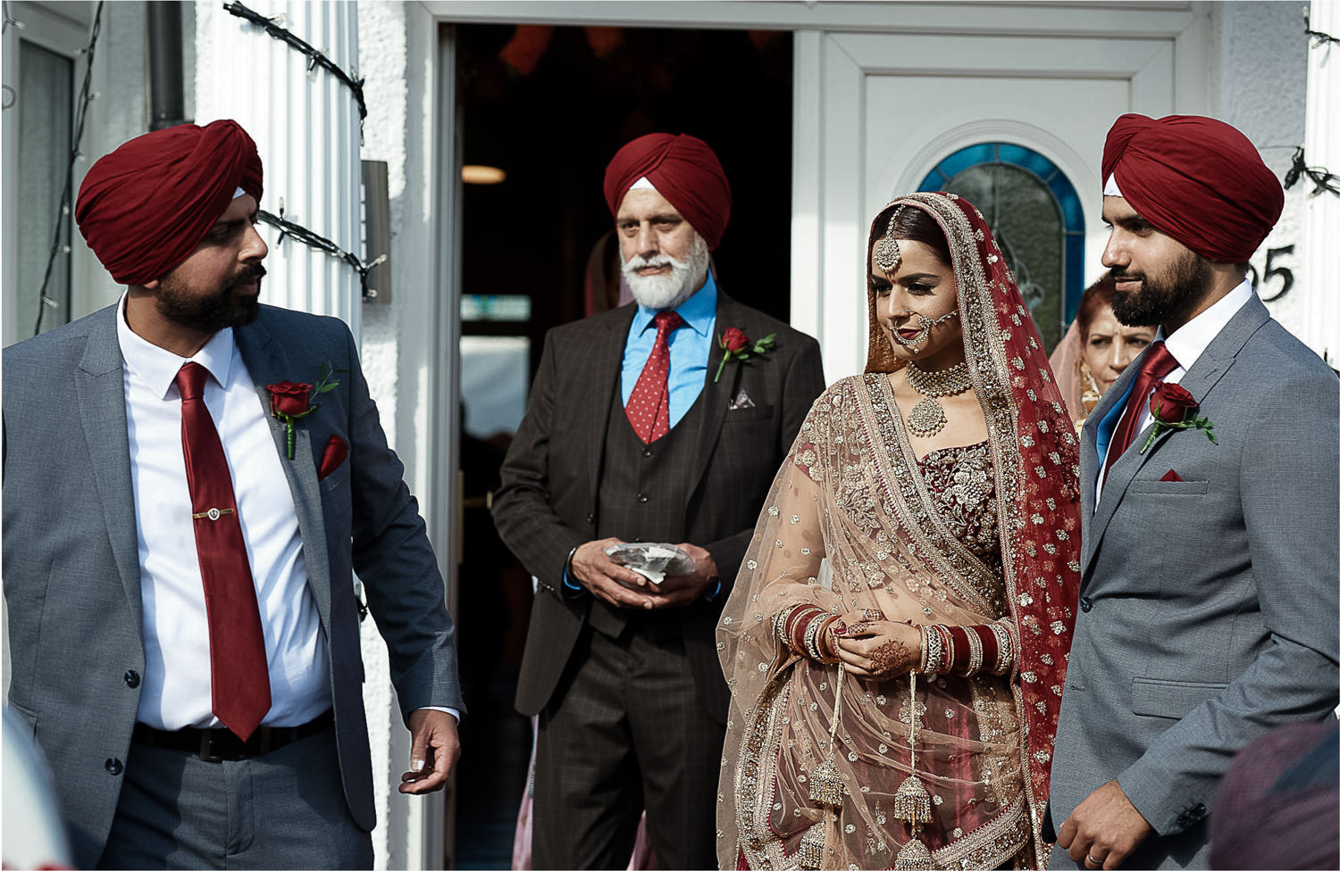 Father and brothers leading indian bride out of her house in the morning