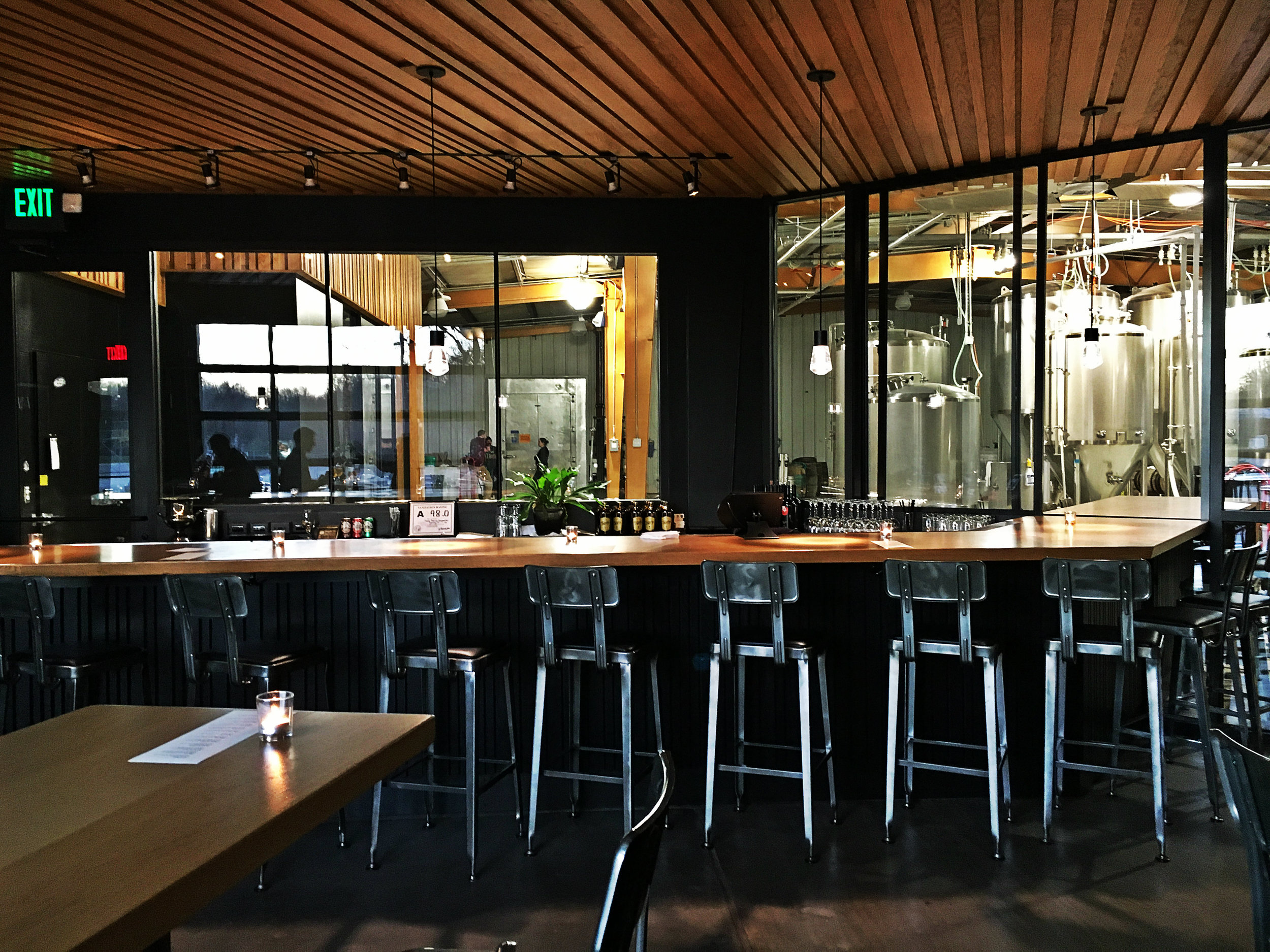 Taproom bar with views into the brewery beyond.