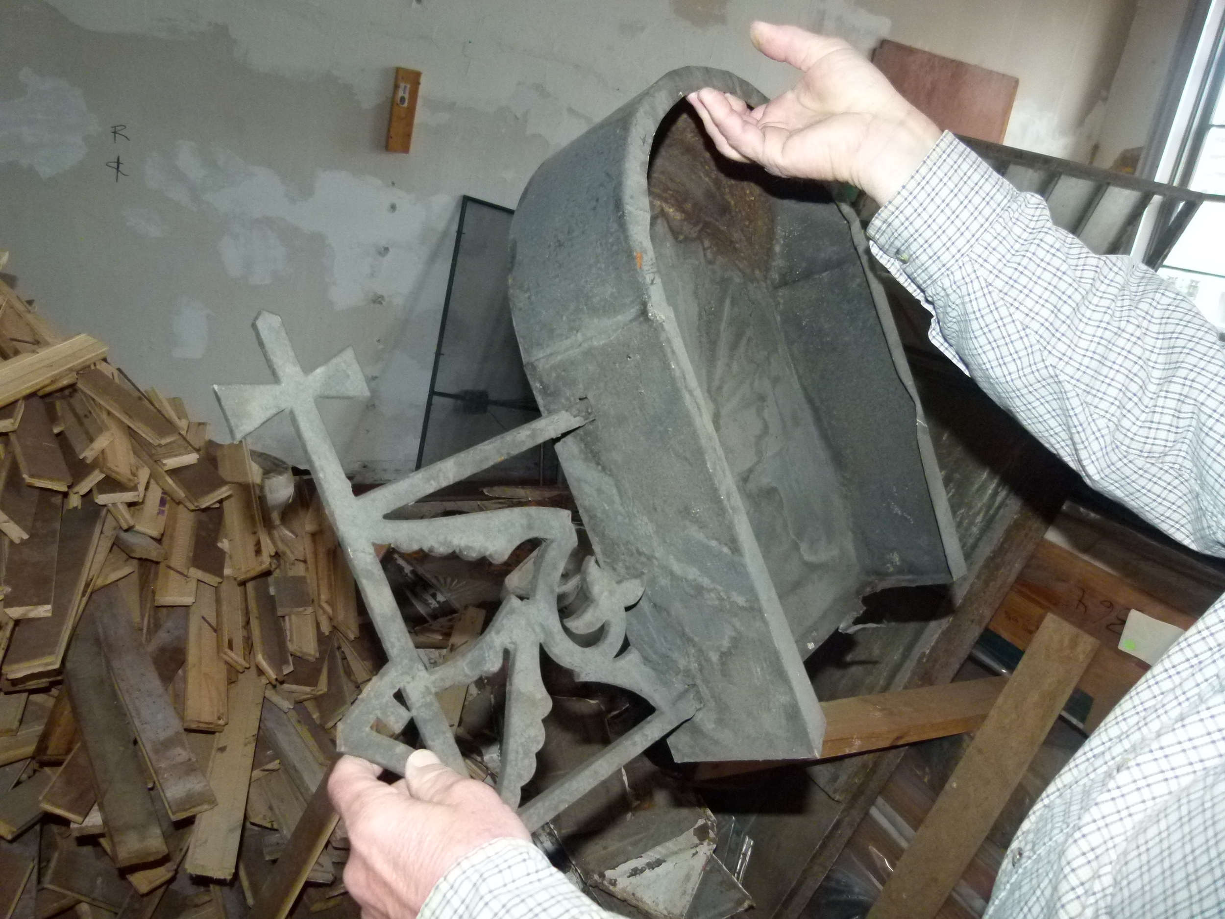 The contractor holds up the decorative metal fragment found in the 19th century building