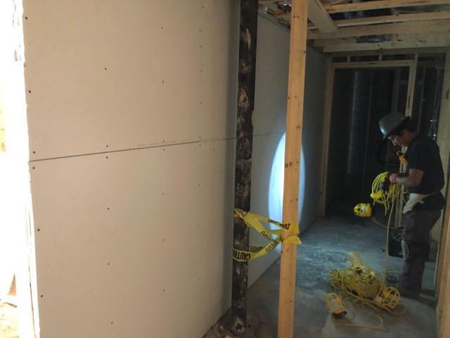 Sheetrock being put in the bathroom hallway.