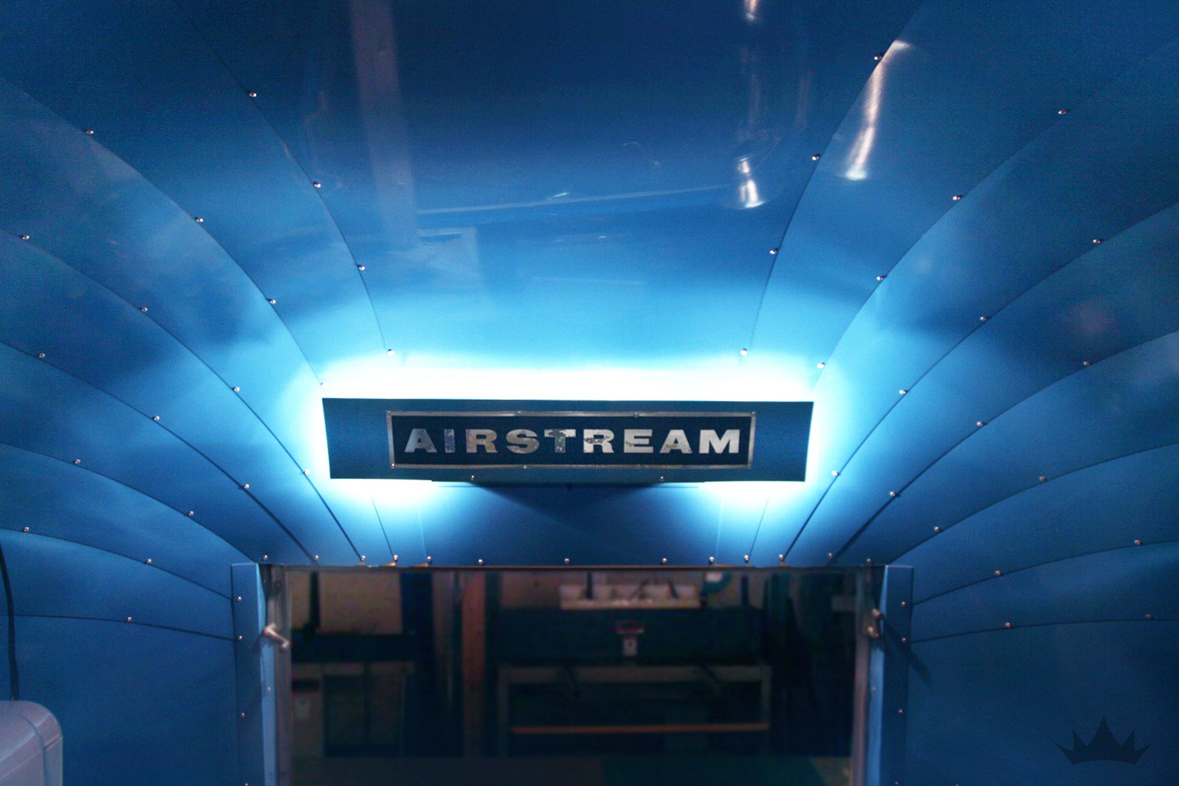 It doesn't get more custom than this! An Airstream emblem -turned light valance was the perfect finishing touch for an already Airstream blue bathroom.