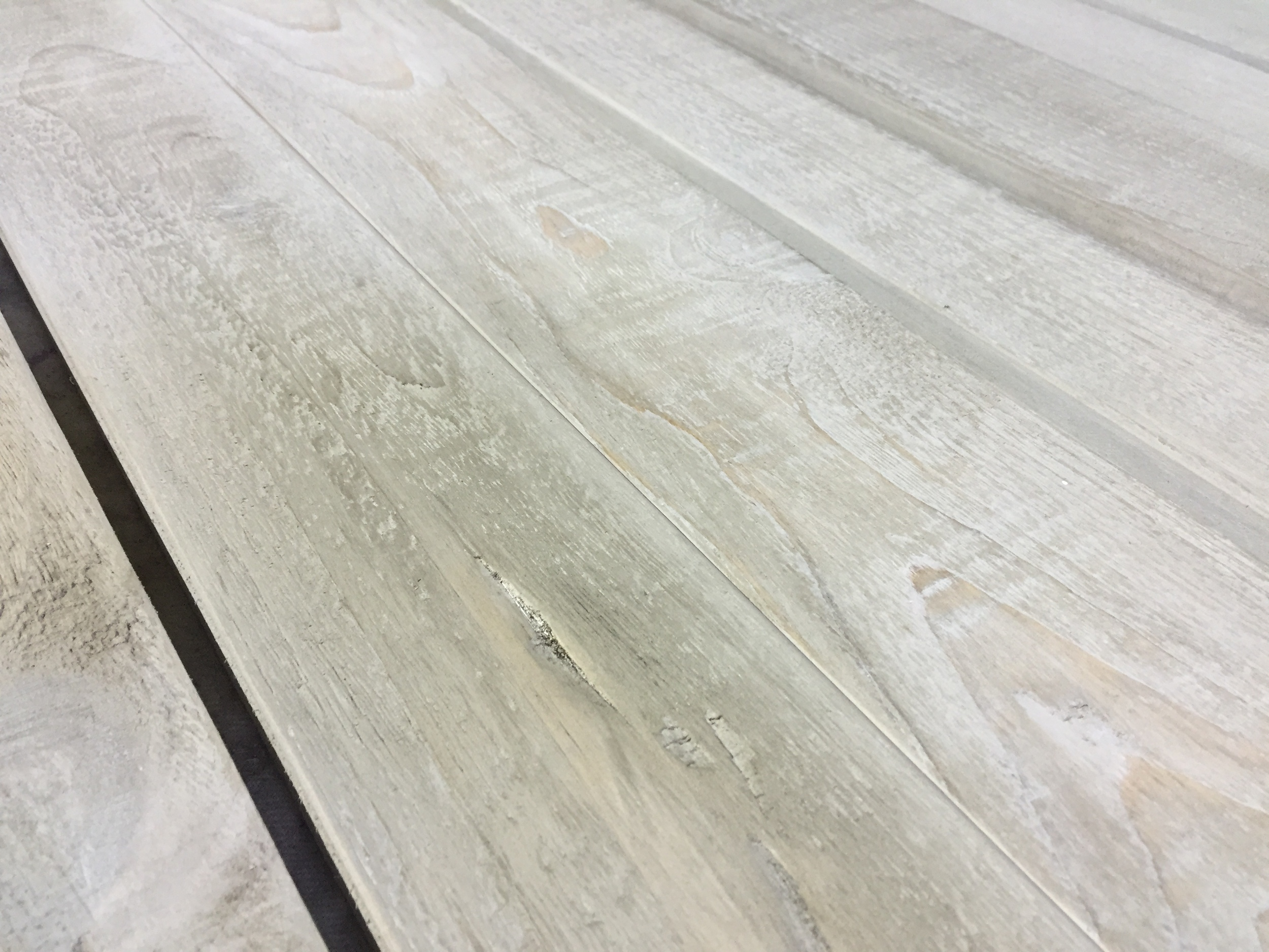 White wash settling into the cracks helps create that worn look. If you wet sanded and packed those fibers in there like we did, it mixes in and solidifies to create complex shapes and subtle shadows.
