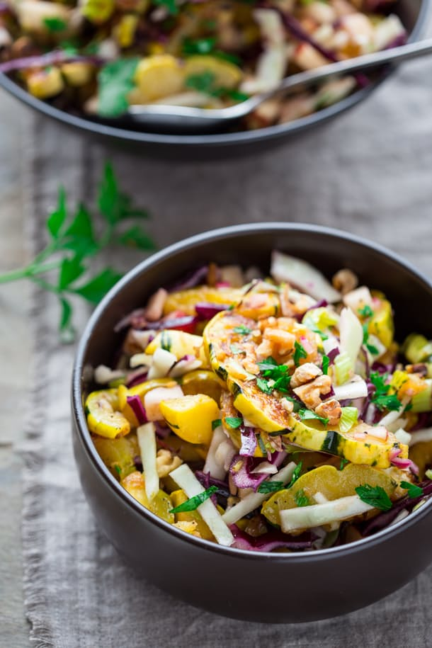 INGREDIENTS   2 medium delicata squash 3 tablespoons extra-virgin olive oil, divided 1 1/4 teaspoon coarse kosher salt 1/2 teaspoon freshly ground pepper, divided 3 tablespoons red wine vinegar 2 teaspoons honey (or use agave to make it vegan) 1/4 teaspoon caraway seed 1/4 cup minced red onion 2 cups shredded cabbage 1 large apple, finely diced 1/2 cup chopped celery hearts (preferably with leaves) 1/2 cup chopped toasted walnuts 2 tablespoons Italian parsley, cut into strips (optional)      INSTRUCTIONS   Cut delicata in half lengthwise; scoop out seeds and pulp. Cut lengthwise again, and then into 1/4-inch quarter-moons. Toss delicata in a medium bowl with 1 tablespoon oil, 1/2 teaspoon salt, and 1/4 teaspoon pepper until coated. Spread out in a single layer onto a large rimmed baking sheet. Roast, stirring once or twice, until tender and darkened in spots, 16 to 20 minutes.  Meanwhile combine vinegar, honey, caraway, the remaining 3/4 teaspoon salt, and the remaining 1/4 teaspoon pepper in a microwave-safe measuring cup or bowl. Microwave until boiling-hot, 1 to 1 1/2 minutes. Remove from the microwave and stir in onion. Set aside for 10 minutes. Whisk in the remaining 2 tablespoons oil.  Toss cabbage, apple, celery hearts, the hot roasted delicata squash, and the warm pickled onion dressing in a large salad bowl. Divide among four plates and top with walnuts and parsley (if using).
